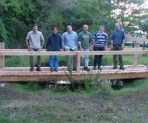 Volunteers and rangers with a bridge they built