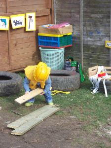 Child playing in the garden with toys