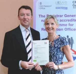Lois with the government's General Register Office Deputy Registrar General Andrew Dent receiving her certificate